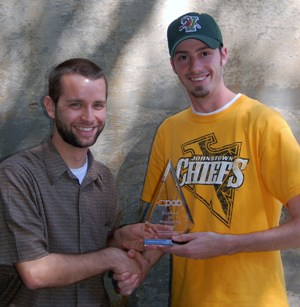 """""""Global Alert"""" producer Mike Wilson hands off the PAB award to communications media professor Zachary J. Stiegler, Ph.D., faculty adviser to WIUP-FM, Davis Hall, May 7, 2010. Photo by David Loomis."""