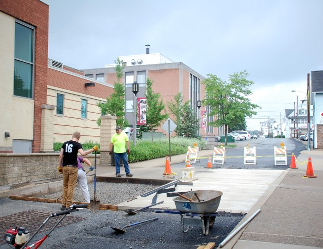 Workers pour one of two new concrete walkways/speed bumps on West Avenue between the Hadley Union Building complex adjacent to the IUP campus, June 19. Photo by David Loomis.
