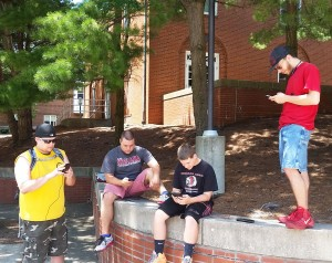 Ethan A. Isenberg, 25, of Homer City (left), and Chad A. Corle, 24, Justice S. Cowen, 14, and David C. Williams III, 28, of Indiana, play Pokemon Go on Indiana University of Pennsylvania's campus, July 11. Photo by Ethan Brogan.
